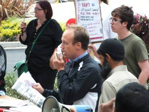 Socialist Party member Paul Hunt speaking at the protest. Anti-war placard from Israel can be seen in the background - in Hebrew, Arabic and English